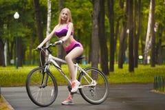 Dziewczyna jedzie jej rower na słonecznym dniu Fotografia Stock