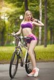 Dziewczyna jedzie jej rower w słonecznym dniu i pięknym Fotografia Stock