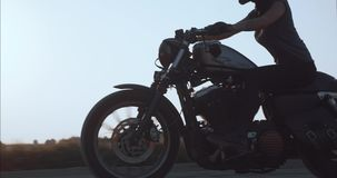 Dziewczyna jedzie motocykl jedzie wzdłuż wiejskiej drogi przy zmierzchu bocznym widokiem zbiory