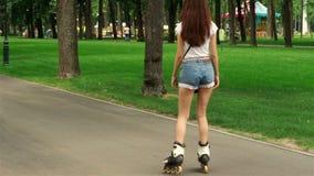 Dziewczyna jedzie na rolownikach z nikłymi nogami w skrótach zbiory