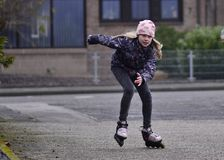Dziewczyna jedzie rolkowe łyżwy zestrzela ulicę zdjęcia stock