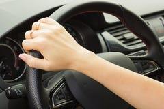 Dziewczyna jedzie samochód, trzyma kierownicę z jeden ręką obrazy stock