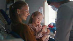 Dziewczyna, jej mama i dentysta w stomatologicznym biurze stomatologist radzi z specjalną zabawką zbiory