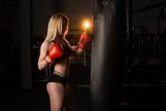 Dziewczyna jest bokserska uderzający pięścią torby gym zdjęcia royalty free