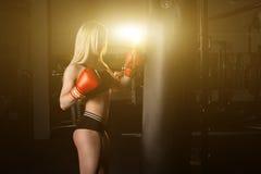 Dziewczyna jest bokserska uderzający pięścią torby gym Obraz Stock