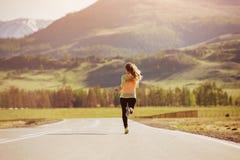 Dziewczyna jest działającymi zmierzch drogi górami Zdjęcia Royalty Free