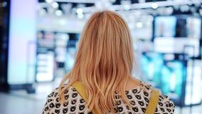 Dziewczyna jest jaskrawym centrum handlowym odosobniony tylni widok biel Wolny playback zdjęcie wideo
