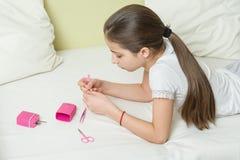 Dziewczyna jest 10 lat na łóżku w ona w domu domowi ubrania, przybija ona gwoździe używać manicure akcesoria zdjęcie stock