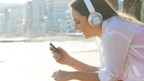 Dziewczyna jest oglądająca środki na mądrze telefonie i słuchająca zdjęcie wideo