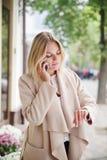 Dziewczyna jest przyglądająca zegar i opowiadający na telefonie zdjęcie stock