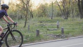Dziewczyna jest ubranym błękitnego bydło i czarnego hełm jedzie bicykl w parku Drogowy kolarstwa szkolenie Kolarstwa poj?cie zbiory wideo