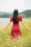 Dziewczyna jest ubranym czerwieni suknię w pszenicznym polu Obrazy Royalty Free