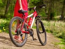 Dziewczyna jest ubranym czerwoną polek kropek suknię jedzie bicykl w parka Zdjęcie Stock