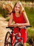 Dziewczyna jest ubranym czerwoną polek kropek suknię jedzie bicykl w parka Zdjęcia Royalty Free