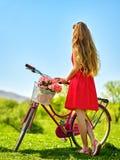 Dziewczyna jest ubranym czerwoną polek kropek suknię jedzie bicykl w parka Obraz Stock