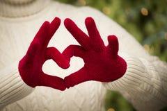 Dziewczyna Jest ubranym Czerwone mitynki Robi Kierowej ręce Podpisywać Fotografia Stock