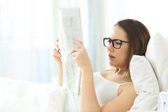 Dziewczyna jest ubranym eyeglasses ma problemy czytać gazetę obrazy royalty free