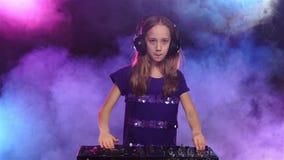 Dziewczyna jest ubranym hełmofony i zaczyna sztuki na turntable swobodny ruch zbiory wideo