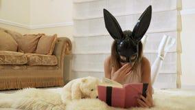 Dziewczyna jest ubranym królik maskę czyta książkę kłaść na podłoga zbiory wideo