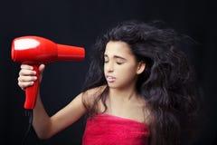 Dziewczyna jest ubranym ręcznikową osuszkę jej włosy z hairdryer Obrazy Stock