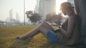 Dziewczyna jest ubranym słomianego kapelusz z kędzierzawym włosy siedzi na trawie, używać wiszącą ozdobę zbiory wideo
