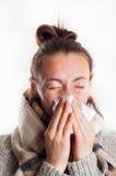 Dziewczyna jest ubranym szalika i sweate z zimnym kichnięciem w chusteczce Fotografia Stock