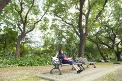 Dziewczyna jest ubranym szkła siedzi na ławce Fotografia Stock