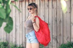 Dziewczyna jest ubranym szkła, drelichowi skróty, szara koszula z plecakiem Zdjęcia Stock