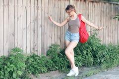 Dziewczyna jest ubranym szkła, drelichowi skróty, szara koszula z plecakiem Zdjęcie Stock