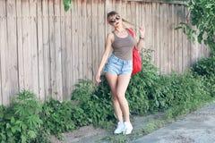 Dziewczyna jest ubranym szkła, drelichowi skróty, szara koszula z plecakiem Obraz Stock