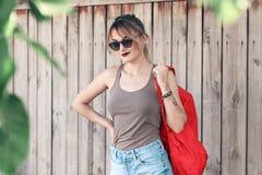 Dziewczyna jest ubranym szkła, drelichowi skróty, szara koszula z plecakiem Fotografia Stock