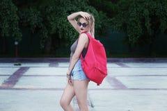 Dziewczyna jest ubranym szkła, drelichowi skróty, szara koszula z plecakiem Zdjęcie Royalty Free