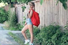 Dziewczyna jest ubranym szkła, drelichowi skróty, szara koszula z plecakiem Fotografia Royalty Free