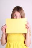 Dziewczyna jest ubranym yelow odziewa pustą kartę i pokazuje Fotografia Stock
