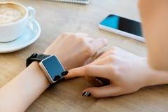 Dziewczyna jest ubranym zegarek, filiżanka kawy na stole Fotografia Royalty Free
