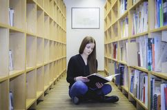 Dziewczyna jest usytuowanym na bibliotecznej podłoga Obraz Stock
