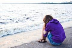 Dziewczyna jest usytuowanym przy brzeg rzeki Zdjęcia Stock