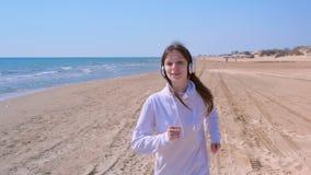 Dziewczyna jogging w hełmofonach słucha muzycznego przerwa bieg łapać oddechu sport plenerowego zbiory wideo