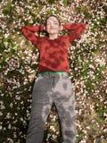Dziewczyna kłama na trawie, zakrywającej z białymi kwiatami fotografia stock
