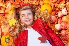 Dziewczyna kłaść na liściach z baniami, jabłka Fotografia Stock