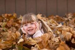 Dziewczyna kłaść w liścia stosu sztuki bawić się Obrazy Royalty Free