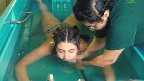 Dziewczyna kłama na jej żołądku w skąpaniu zwolnione tempo, podczas gdy masuje jej szyję podczas wodnej masaż sesi zbiory