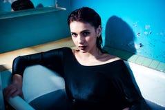 Dziewczyna kłama w łazience z barwioną purpury wodą z nagimi ramionami piękna błękitny jaskrawy pojęcia twarzy mody makeup kobiet obraz royalty free