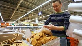 Dziewczyna klient wybiera deser na kontuarze supermarket zbiory