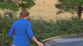 Dziewczyna komes frontowa część samochód i openes okapturzamy Dymny początek bieg od silnika Dziewczyna próbuje trząść jej rękę n zbiory wideo