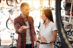 Dziewczyna konsultant pokazuje nabywcy w rowerowym sklepie obraz stock
