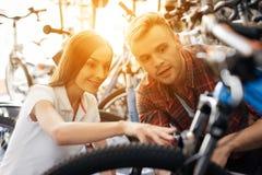 Dziewczyna konsultant pokazuje nabywcy w rowerowym sklepie fotografia royalty free