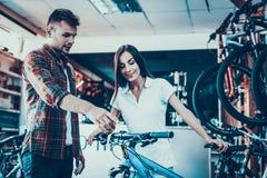 Dziewczyna konsultanta przedstawienia cykl nabywca w sporta sklepie obrazy royalty free