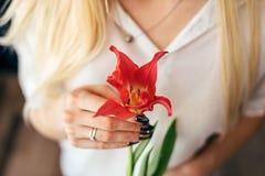 Dziewczyna która siedzi na podłoga trzyma różowego tulipanu zdjęcia stock