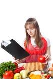 Dziewczyna kucharz przygotowywa według książki obrazy stock